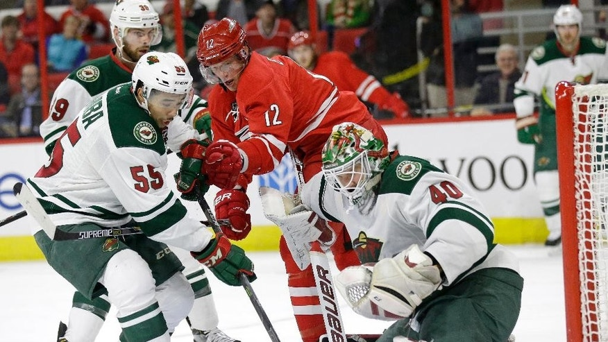 Carolina Hurricanes' Eric Staal (12) tries to shoot against Minnesota Wild's Matt Dumba (55) and goalie Devan Dubnyk (40) during the second period of an NHL hockey game in Raleigh, N.C., Friday, March 6, 2015. (AP Photo/Gerry Broome)