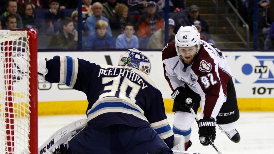 Colorado Avalanche' Gabriel Landeskog, right, of Sweden, shoots the puck against Columbus Blue Jackets goalie Curtis McElhinney during the first period of an NHL hockey game in Columbus, Ohio, Saturday, March 7, 2015. Landeskog scored on the play. (AP Photo/Paul Vernon)