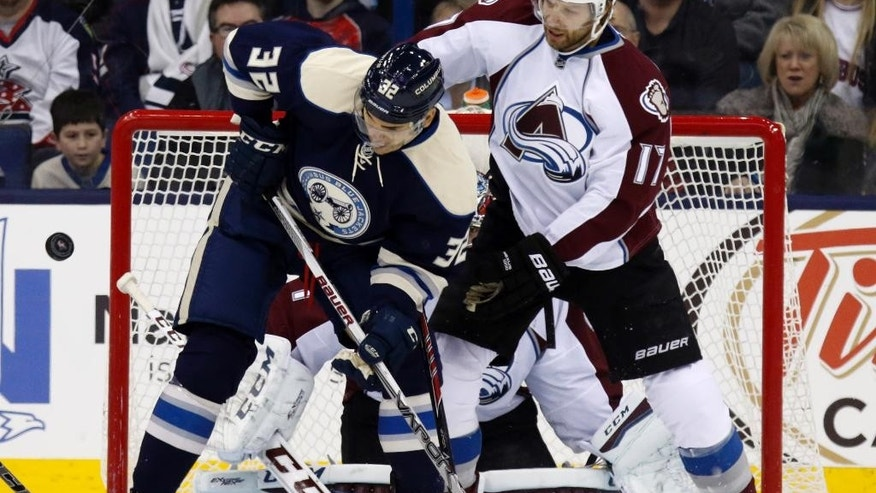 Columbus Blue Jackets' Rene Borque, left, works for the puck against Colorado Avalanche's Brad Stuart during the first period of an NHL hockey game in Columbus, Ohio, Saturday, March 7, 2015. (AP Photo/Paul Vernon)