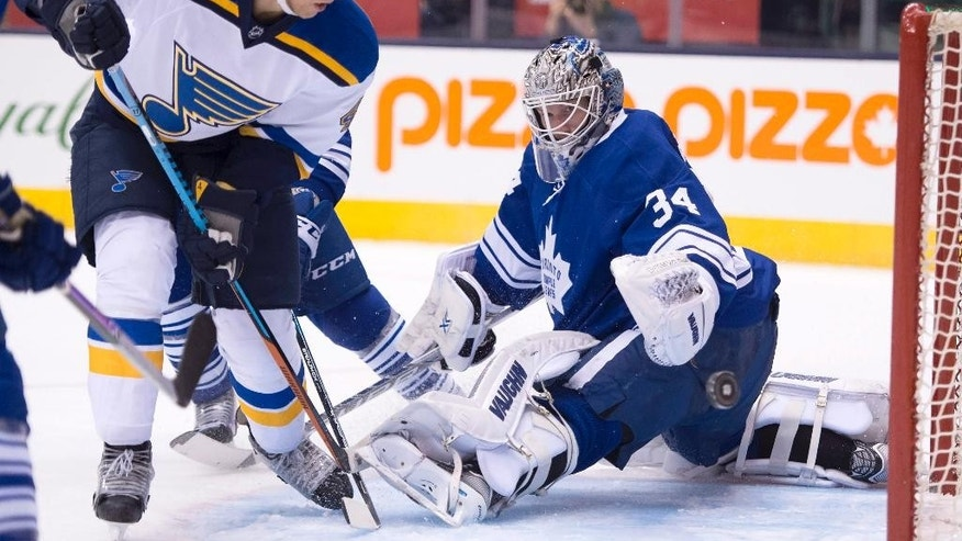 Toronto Maple Leafs goaltender James Reimer makes a save on St Louis Blues defenseman Carl Gunnarsson during the third period of an NHL hockey game Saturday, March 7, 2015, in Toronto. (AP Photo/The Canadian Press, Frank Gunn)