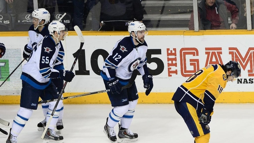 Winnipeg Jets right wing Drew Stafford (12) and Nashville Predators left wing James Neal, right, return to their benches after Stafford scored an open-net goal in the third period of an NHL hockey game against the Nashville Predators Saturday, March 7, 2015, in Nashville, Tenn. Winnipeg won 3-1. (AP Photo/Mark Zaleski)