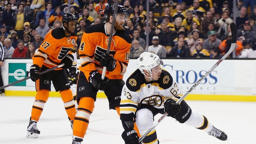 Boston Bruins' Brad Marchand (63) watches his game-winning goal in front of Philadelphia Flyers' Sean Couturier (14) and Wayne Simmonds (17) during overtime in an NHL hockey game in Boston, Saturday, March 7, 2015. The Bruins won 3-2. (AP Photo/Michael Dwyer)