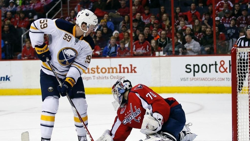 Buffalo Sabres left wing Tim Schaller (59) cannot get the puck past Washington Capitals goalie Braden Holtby (70) in the second period of an NHL hockey game Saturday, March 7, 2015, in Washington. (AP Photo/Alex Brandon)