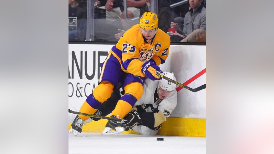 Pittsburgh Penguins center Evgeni Malkin, bottom, of Russia, falls as he battles for the puck with Los Angeles Kings right wing Dustin Brown during the second period of an NHL hockey game, Saturday, March 7, 2015, in Los Angeles. (AP Photo/Mark J. Terrill)