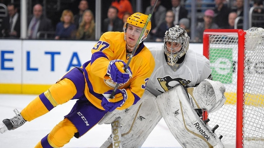 Los Angeles Kings center Nick Shore, left, falls in front of Pittsburgh Penguins goalie Marc-Andre Fleury as the puck is shot during the second period of an NHL hockey game, Saturday, March 7, 2015, in Los Angeles. (AP Photo/Mark J. Terrill)