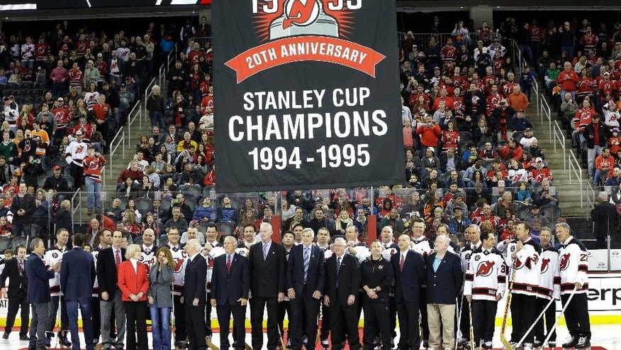 A banner is raised over the New Jersey Devils 1995 Stanley Cup winning team as they are honored before an NHL hockey game against the Philadelphia Flyers, Sunday, March 8, 2015, in Newark, N.J. (AP Photo/Mel Evans)