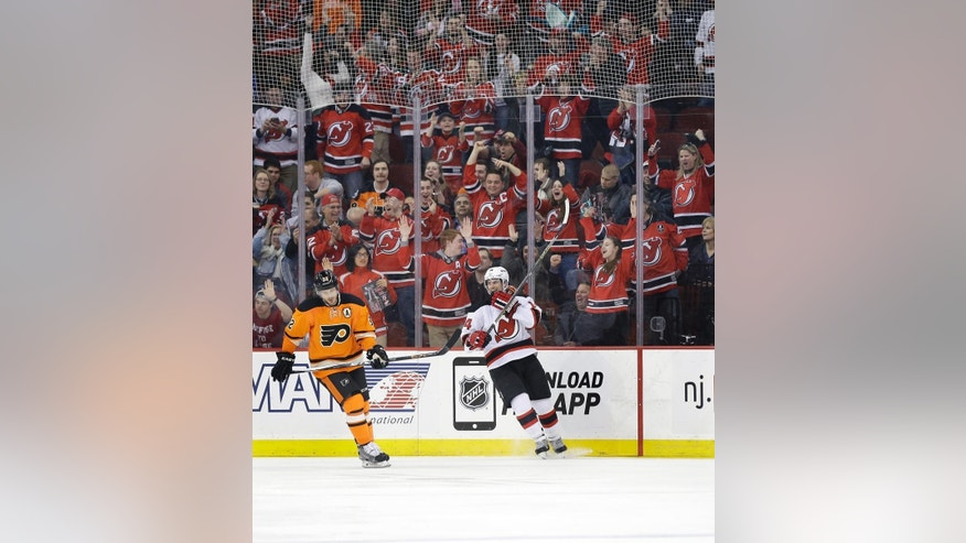 New Jersey Devils' Adam Henrique (14) and fans celebrate his goal as  Philadelphia Flyers' Mark Streit (32), of Switzerland, skates near, during the first period of an NHL hockey game Sunday, March 8, 2015, in Newark, N.J. (AP Photo/Mel Evans)