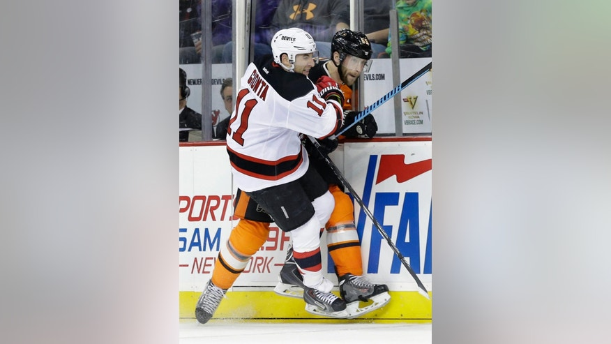 New Jersey Devils' Stephen Gionta (11) checks Philadelphia Flyers' Nick Schultz (55) during the first period of an NHL hockey game Sunday, March 8, 2015, in Newark, N.J. (AP Photo/Mel Evans)