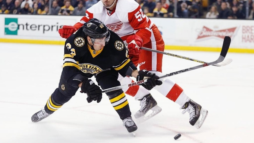 Boston Bruins' Brad Marchand (63) tries to get a shot off as Detroit Red Wings' Jonathan Ericsson (52), of Sweden, defends during the second period of an NHL hockey game in Boston, Sunday, March 8, 2015. (AP Photo/Michael Dwyer)