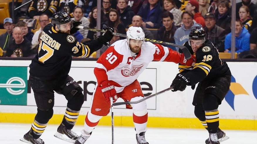 Boston Bruins' Patrice Bergeron (37) and Reilly Smith (18) battle Detroit Red Wings' Henrik Zetterberg (40), of Sweden, for the puck during the first period of an NHL hockey game in Boston, Sunday, March 8, 2015. Smith received a penalty for slashing. (AP Photo/Michael Dwyer)
