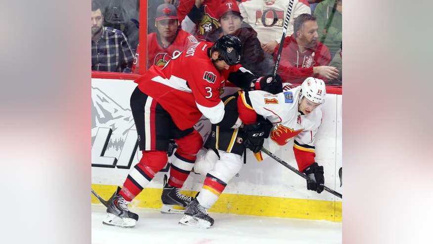 Ottawa Senators' Marc Methot (3) checks Calgary Flames' Mikael Becklund (11) during second period NHL hockey action in Ottawa, Ontario, Sunday, March 8, 2015. (AP Photo/The Canadian Press, Fred Chartrand)