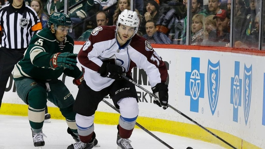 Colorado Avalanche center Joey Hishon (38) controls the puck in front of Minnesota Wild defenseman Matt Dumba (55) during the second period of an NHL hockey game in St. Paul, Minn., Sunday, March 8, 2015. (AP Photo/Ann Heisenfelt)