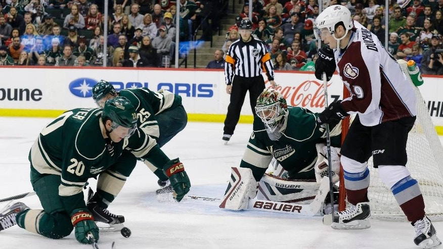 Minnesota Wild defenseman Ryan Suter (20) stops a pass by Colorado Avalanche center Matt Duchene (9) as Wild goalie Devan Dubnyk  covers the net during the second period of an NHL hockey game in St. Paul, Minn., Sunday, March 8, 2015. (AP Photo/Ann Heisenfelt)