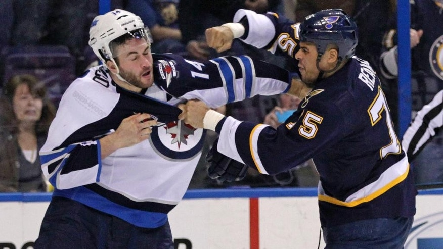 St. Louis Blues' Ryan Reaves (75) fights with Winnipeg Jets' Anthony Peluso (14) during the second period of an NHL hockey game, Tuesday, March 10, 2015, in St. Louis. (AP Photo/Tom Gannam)