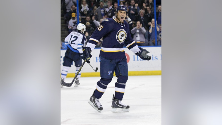 St. Louis Blues' Ryan Reaves celebrates after assisting on a goal by Steve Ott as Winnipeg Jets' Drew Stafford (12) skates back to the bench during the second period of an NHL hockey game, Tuesday, March 10, 2015, in St. Louis. (AP Photo/Tom Gannam)