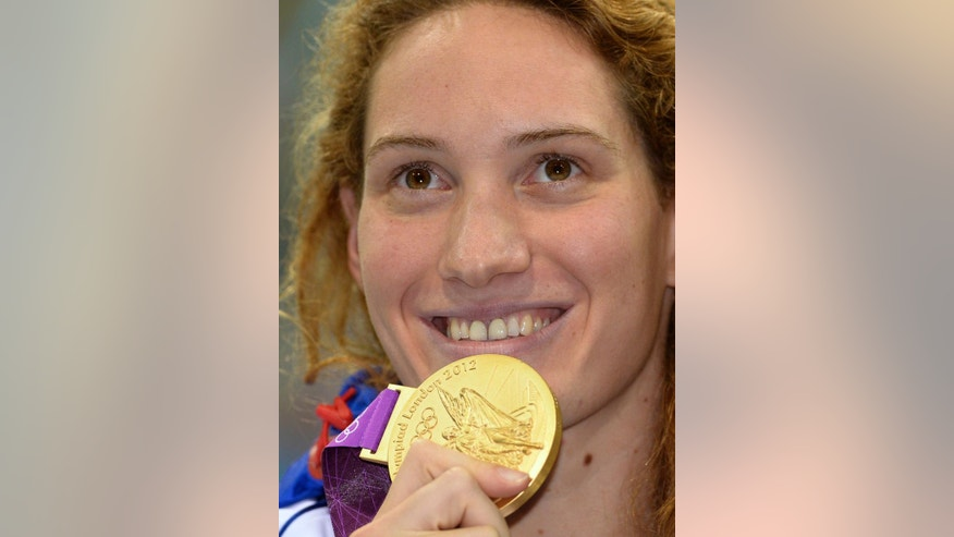 "FILE .- In this Sunday, July 29, 2012 file photo France's Camille Muffat celebrates with her gold medal for the women's 400-meter freestyle swimming final at the Aquatics Centre in the Olympic Park during the 2012 Summer Olympics in London.  Two helicopters carrying passengers filming the popular European reality show ""Dropped"" crashed Monday, March 9, 2015 in a remote area of northwest Argentina, killing all passengers on board including Muffat, according to authorities. (AP Photo/Mark J. Terrill/File)"