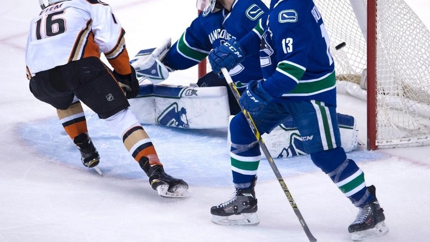 Vancouver Canucks center Nick Bonino (13) looks on as Anaheim Ducks right wing Emerson Etem (16) sends a shot past Canucks goalie Eddie Lack (31) during the third period of NHL action in Vancouver, British Columbia,. Monday, March 9, 2015.(AP Photo/The Canadian Press, Jonathan Hayward)
