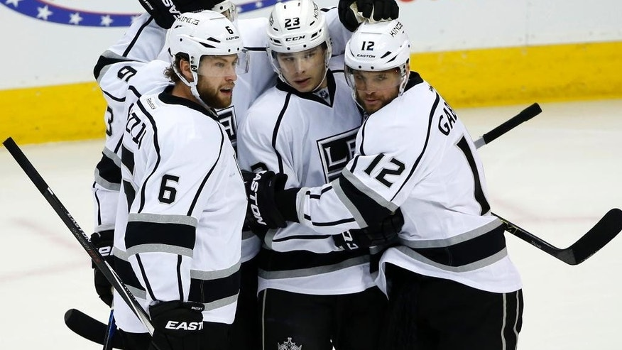 Los Angeles Kings defenseman Jake Muzzin (6), Dustin Brown (23) and Marian Gaborik (12) celebrate Gaborik's goal against the Colorado Avalanche during the first period of an NHL hockey game, Tuesday, March 10, 2015, in Denver. (AP Photo/Jack Dempsey)