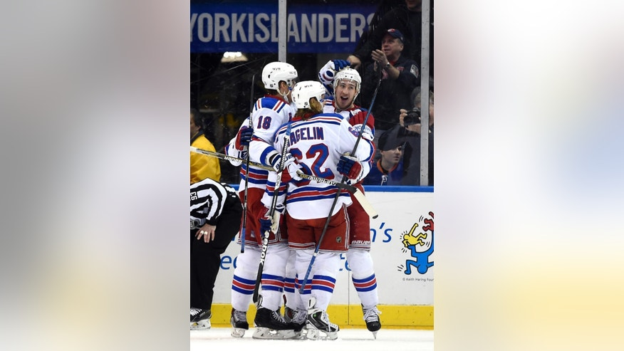 New York Rangers right wing Kevin Hayes, right, defenseman Marc Staal (18) and left wing Carl Hagelin (62) celebrate Hayes's goal in the second period of an NHL hockey game against the New York Islanders Tuesday, March 10, 2015, in Uniondale, N.Y. (AP Photo/Kathy Kmonicek)