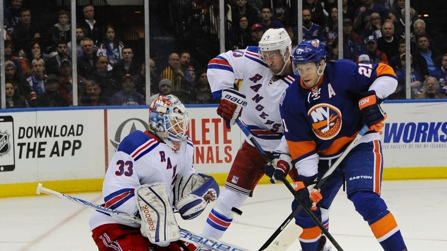 New York Rangers goalie Cam Talbot (33) blocks a shot on goal by New York Islanders right wing Kyle Okposo (21) as Rangers right wing Kevin Hayes (13) defends in the second period of an NHL hockey game Tuesday, March 10, 2015, in Uniondale, N.Y. (AP Photo/Kathy Kmonicek)