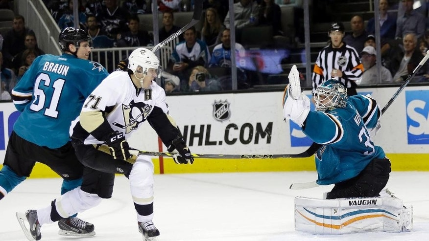 San Jose Sharks goalie Antti Niemi, right, stops a shot from Pittsburgh Penguins' Evgeni Malkin (71) during the second period of an NHL hockey game Monday, March 9, 2015, in San Jose, Calif. (AP Photo/Marcio Jose Sanchez)