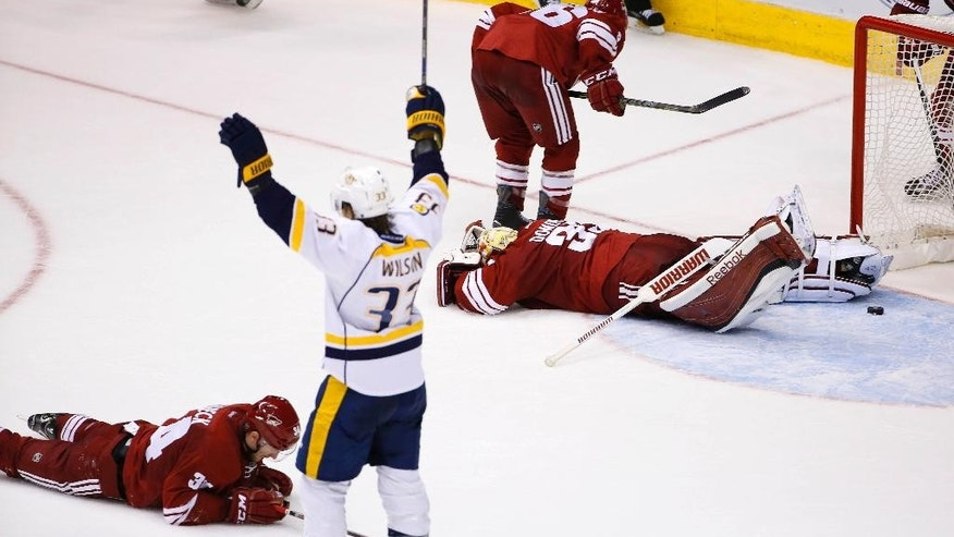 Nashville Predators' Colin Wilson (33) celebrates a game-winning goal by teammate James Neal as Arizona Coyotes' Louis Domingue, right, Klas Dahlbeck, left, of Sweden, and Mark Arcobello, top, react during overtime of an NHL hockey game Monday, March 9, 2015, in Glendale, Ariz.  The Predators won 2-1. (AP Photo/Ross D. Franklin)
