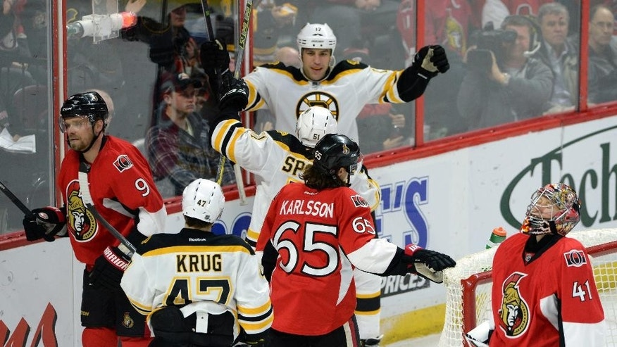 Ottawa Senators' Milan Michalek, left to right, Erik Karlsson, and Craig Anderson react to a goal by Boston Bruins' Ryan Spooner, center, as he celebrates with teammate Milan Lucic during second period NHL hockey action in Ottawa, Ontario, on Tuesday, March 10, 2015. (AP Photo/The Canadian Press, Sean Kilpatrick)
