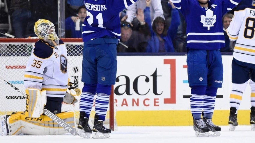 Toronto Maple Leafs' Tyler Bozak (42) celebrates his game-tying goal with teammate James van Riemsdyk (21) as Buffalo Sabres goalie Anders Lindback reacts during the third period of an NHL hockey game in Toronto, Wednesday, March 11, 2015. (AP Photo/The Canadian Press, Frank Gunn)