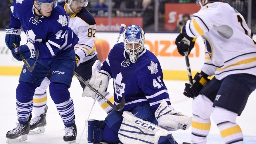 Toronto Maple Leafs goalie Jonathan Bernier makes a glove save as Buffalo Sabres' Marcus Foligno (82) and Brian Gionta (12) look for a rebound and Maple Leafs' Morgan Rielly (44) defends during the first period of an NHL hockey game in Toronto, Wednesday, March 11, 2015. (AP Photo/The Canadian Press, Frank Gunn)