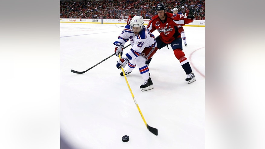 New York Rangers right wing Martin St. Louis (26) prepares to pass the puck with Washington Capitals left wing Jason Chimera (25) defending during the second period of an NHL hockey game Wednesday, March 11, 2015, in Washington. (AP Photo/Alex Brandon)