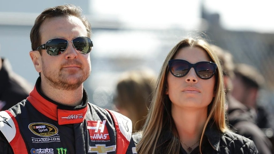 FILE - In this Feb. 15, 2015, file photo, driver Kurt Busch, left, stands with his girlfriend, Ashley Van Metre, before getting in his car during qualifying for the Daytona 500 NASCAR Sprint Cup Series auto race at Daytona International Speedway in Daytona Beach, Fla. NASCAR lifted its suspension of Kurt Busch on Wednesday, March 11, 2015,  and ruled the former champion can compete in the title Chase should he qualify. Busch missed the first three races of the season when NASCAR suspended him for an alleged domestic assault on his ex-girlfriend. The Delaware attorney general last week declined to charge Busch for the September incident with Patricia Driscoll. (AP Photo/John Raoux, File)