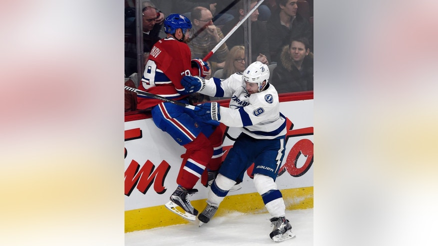 Montreal Canadiens defenseman Andrei Markov, left, is checked into the boards by Tampa Bay Lightning center Tyler Johnson (9) during the second period of an NHL hockey game Tuesday, March 10, 2015, in Montreal. (AP Photo/The Canadian Press, Ryan Remiorz)