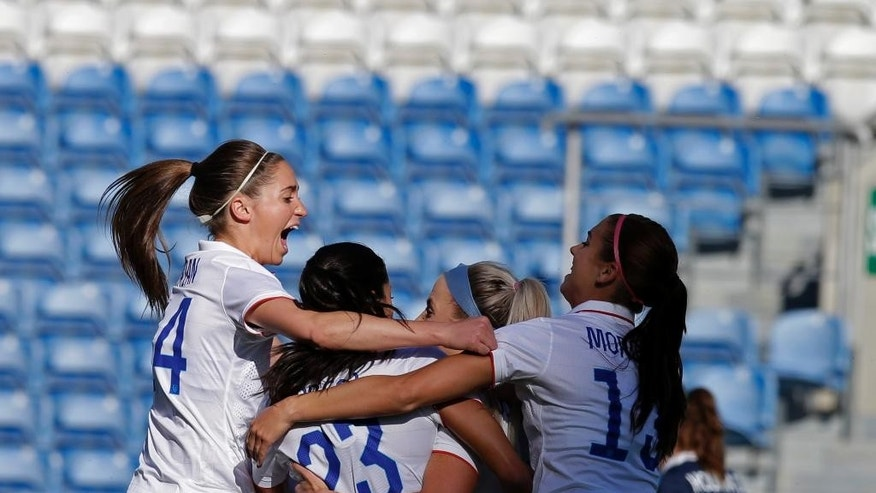 Julie Johnston, partially seen second right, of the US, celebrates with teammates after scoring the opening goal against France, during the women's soccer Algarve Cup final match between US and France at the Algarve stadium, outside Faro, southern Portugal, Wednesday, March 11, 2015. (AP Photo/Francisco Seco)