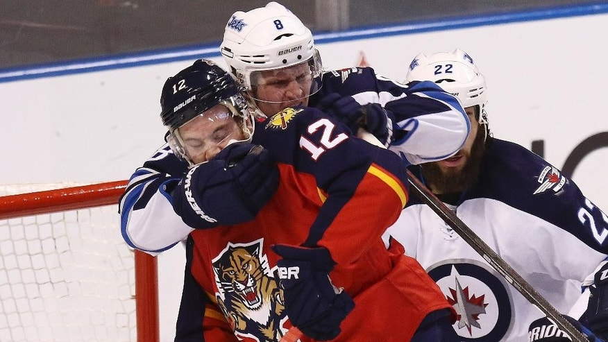 Winnipeg Jets' Jacob Trouba (8) wrestles Florida Panthers' Jimmy Hayes (12) away from the net during the first period of an NHL hockey game in Sunrise, Fla., Thursday, March 12, 2015. (AP Photo/J Pat Carter)