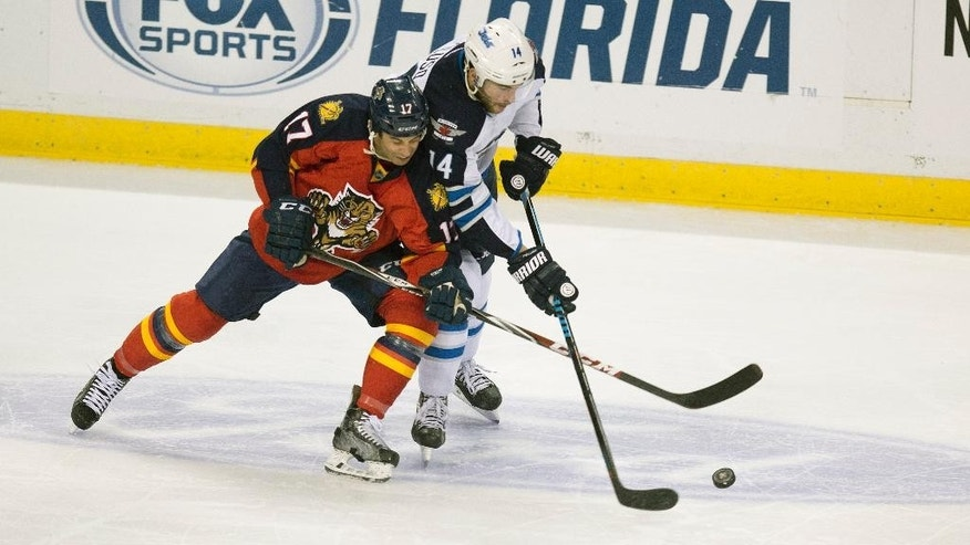 Florida Panthers' Derek MacKenzie (17) and Winnipeg Jets' Anthony Peluso (14) battle for the puck during the second period of an NHL hockey game in Sunrise, Fla., Thursday, March 12, 2015. (AP Photo/J Pat Carter)