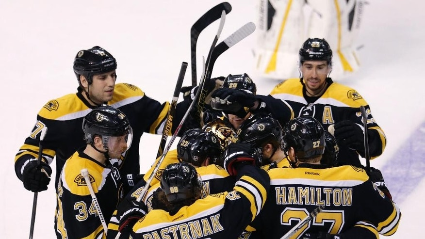 Boston Bruins goalie Tuukka Rask and left wing Brad Marchand are congratulated by teammates after a win against the Tampa Bay Lightning after a shootout during an NHL hockey game in Boston, Thursday, March 12, 2015. The Bruins defeated the Lightning 3-2. (AP Photo/Charles Krupa)