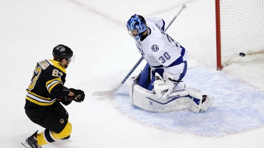 Boston Bruins left wing Brad Marchand (63) beats Tampa Bay Lightning goalie Ben Bishop (30) for the game-winning shot in a shootout during an NHL hockey game in Boston, Thursday, March 12, 2015. The Bruins defeated the Lightning 3-2. (AP Photo/Charles Krupa)