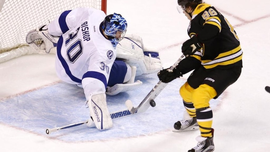 Tampa Bay Lightning goalie Ben Bishop (30) makes a stick-save on a shot by Boston Bruins right wing David Pastrnak (88) during overtime of an NHL hockey game in Boston, Thursday, March 12, 2015. (AP Photo/Charles Krupa)