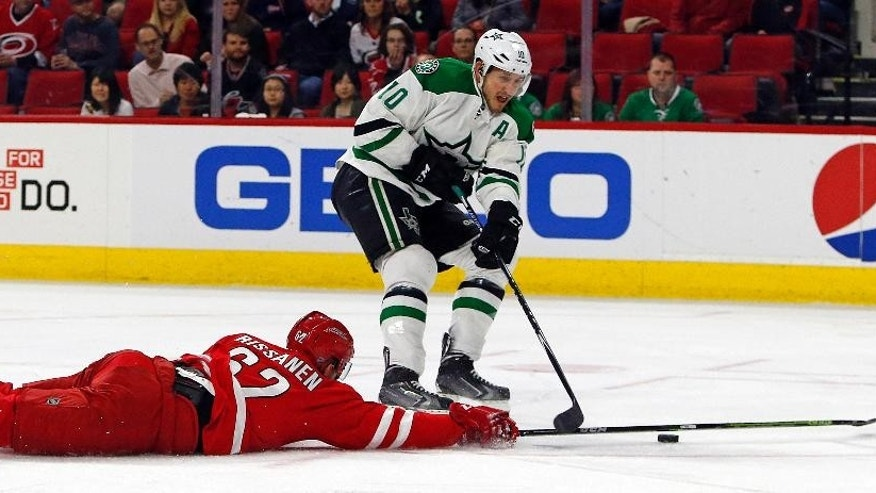 Dallas Stars' Shawn Horcoff (10) has the puck poked away by Carolina Hurricanes' Rasmus Rissanen (62), of Finland, during the first period of an NHL hockey game, Thursday, March 12, 2015, in Raleigh, N.C. (AP Photo/Karl B DeBlaker)
