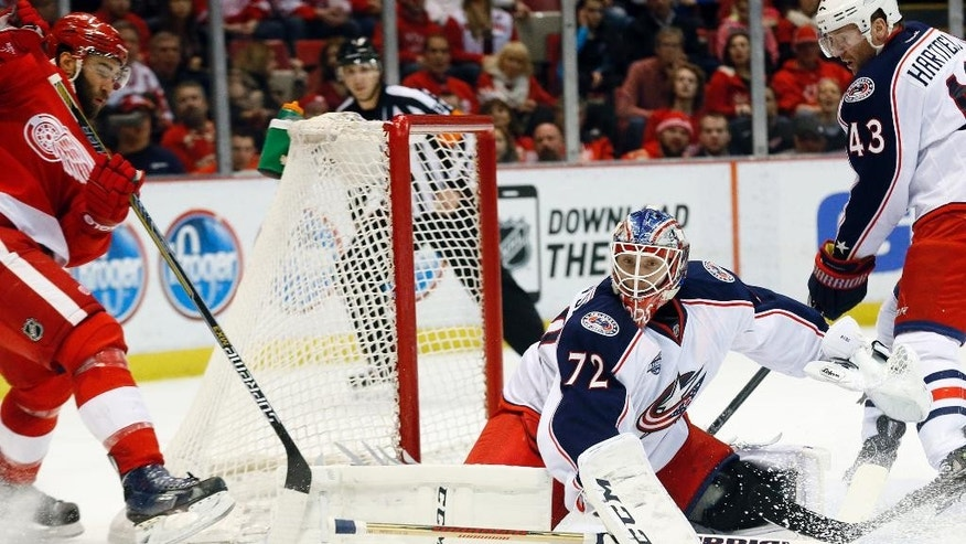 Columbus Blue Jackets goalie Sergei Bobrovsky (72) stops a Detroit Red Wings defenseman Kyle Quincey (27) shot in the second period of an NHL hockey game in Detroit Thursday, March 12, 2015. (AP Photo/Paul Sancya)