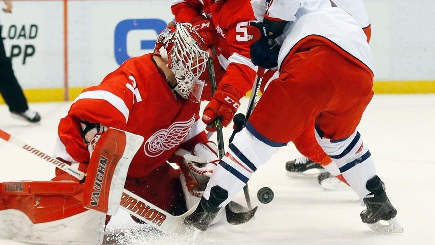 Detroit Red Wings goalie Jimmy Howard (35) stops a Columbus Blue Jackets right wing Cam Atkinson (13) shot as defenseman Niklas Kronwall (55) defends in the first period of an NHL hockey game in Detroit Thursday, March 12, 2015. (AP Photo/Paul Sancya)