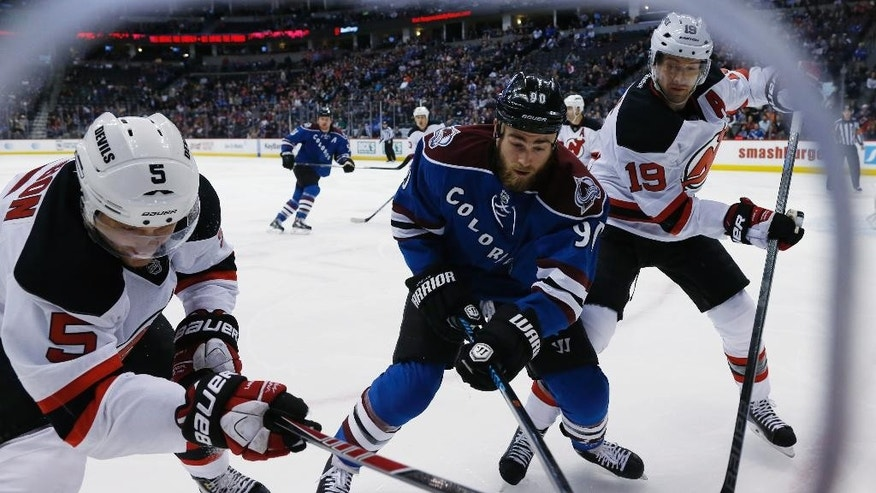 Colorado Avalanche center Ryan O'Reilly, center, fights for control of the puck in the corner with New Jersey Devils defenseman Adam Larsson, left, of Sweden, and center Travis Zajac, right, in the first period an NHL hockey game Thursday, March 12, 2015, in Denver. (AP Photo/David Zalubowski)