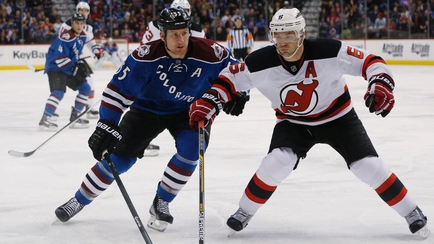 Colorado Avalanche left wing Cody McLeod, left, is checked off the puck by New Jersey Devils defenseman Andy Greene in the first period of an NHL hockey game Thursday, March 12, 2015, in Denver. (AP Photo/David Zalubowski)
