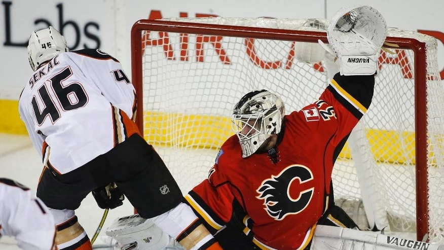 Anaheim Ducks Jiri Sekac, left, from the Czech Republic, has his shot kicked away by Calgary Flames goalie Karri Ramo, from Finland, during first period NHL hockey action in Calgary, Alberta, Wednesday, March 11, 2015.  (AP Photo/The Canadian Press, Jeff McIntosh)