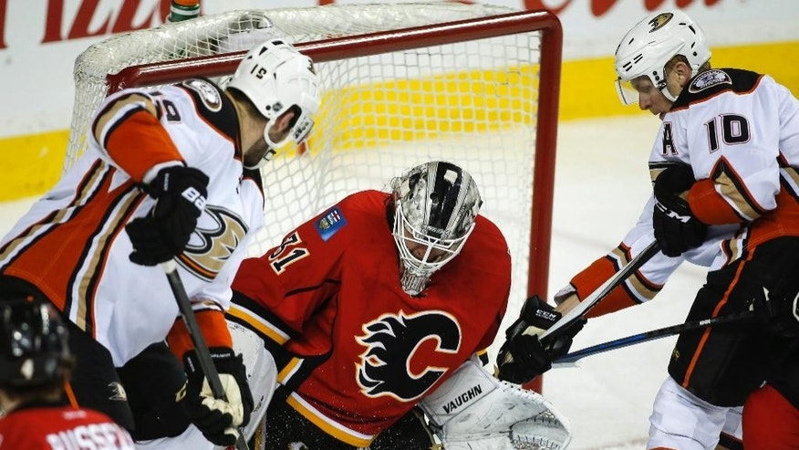 Anaheim Ducks Patrick Maroon, left, and teammate Corey Perry, right, try to get the puck past Calgary Flames goalie Karri Ramo, from Finland, during second period NHL hockey action in Calgary, Alberta, Wednesday, March 11, 2015.  (AP Photo/The Canadian Press, Jeff McIntosh)