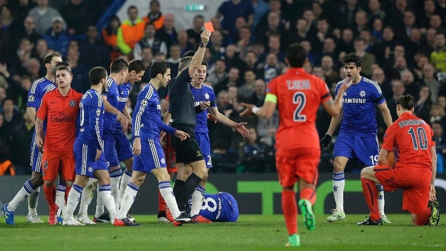 Referee Bjorn Kuipers shows a red card to PSG's Zlatan Ibrahimovic, right,  during the Champions League round of 16 second leg soccer match between Chelsea and Paris Saint Germain at Stamford Bridge stadium in London, Wednesday, March 11, 2015. (AP Photo/Matt Dunham)