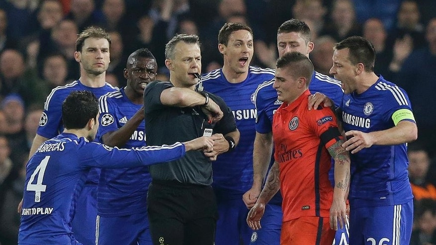 Chelsea players remonstrate with referee Bjorn Kuipers just before he showed a red card to PSG's Zlatan Ibrahimovic during the Champions League round of 16 second leg soccer match between Chelsea and Paris Saint Germain at Stamford Bridge stadium in London, Wednesday, March 11, 2015. (AP Photo/Matt Dunham)
