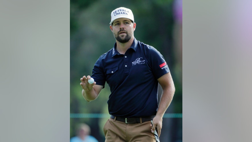 Ryan Moore holds up his golf ball to the gallery after putting out on the fifth hole during the second round of the Valspar Championship golf tournament Friday, March 13, 2015, at Innisbrook in Palm Harbor, Fla. (AP Photo/Chris O'Meara)