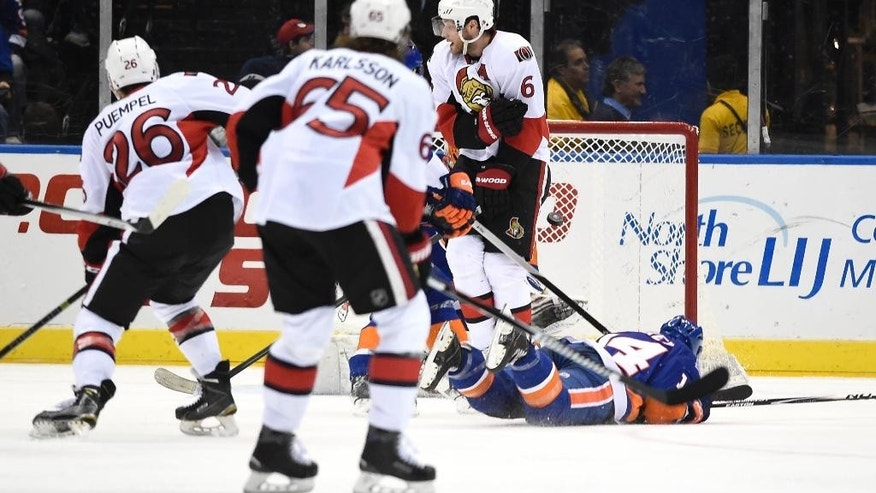 Ottawa Senators left wing Matt Puempel (26) shoots the puck to score as New York Islanders defenseman Thomas Hickey (14), goalie Jaroslav Halak (41) and Senators right wing Bobby Ryan (6) look on in the second period of an NHL hockey game on Friday, March 13, 2015, in Uniondale, N.Y. (AP Photo/Kathy Kmonicek)