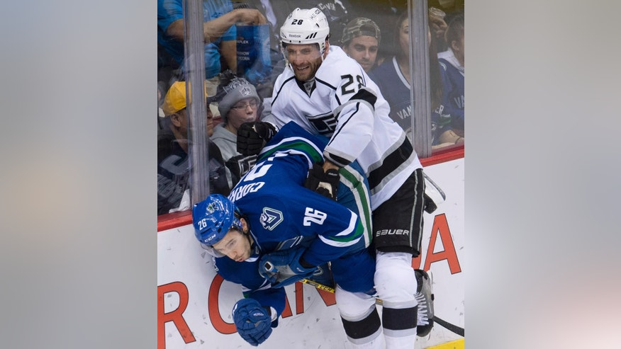 Vancouver Canucks defenseman Frank Corrado (26) goes into the boards with Los Angeles Kings center Jarret Stoll (28) during the second period of an NHL hockey game Thursday, March 12, 2015, in Vancouver, British Columbia. (AP Photo/The Canadian Press, Jonathan Hayward)